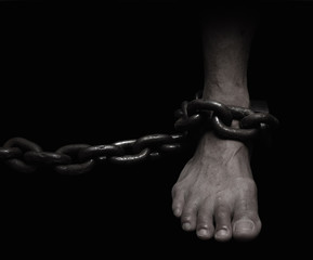 Victim, Slave, Prisoner male foor tied by big metal chain. People have no freedom concept image.