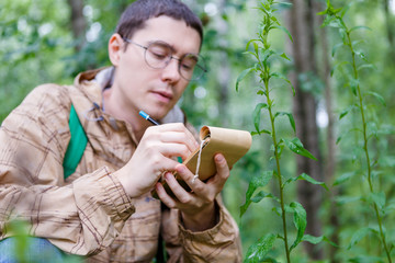 Photo of man writing in notebook among plants