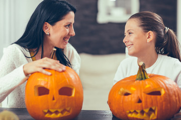 Mother with daughter creating big orange pumpkin for Halloween and having fun Wall mural
