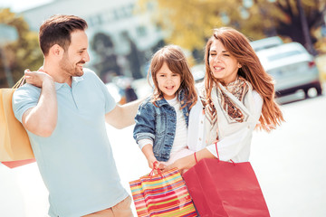Family couple with child and shopping bags outdoors.