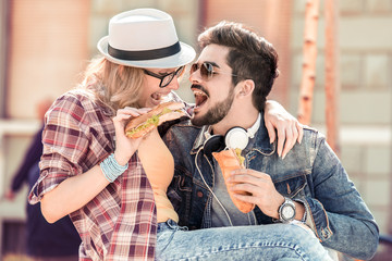 Couple eating and sharing sandwich.