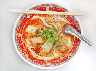 Spicy fish noodle in the bowl with chopsticks and spoon.