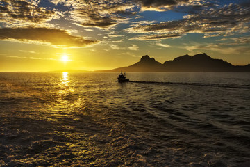 Magical view of the traveler to the sea:  sun at sunset,  mountains, fjord and ship.