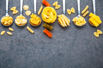 Italian foods concept and menu design. Various kind of Pasta Farfalle, Pasta A Riso, Orecchiette Pugliesi, Gnocco Sardo and Farfalle in metal spoons setup on stone background with flat lay.