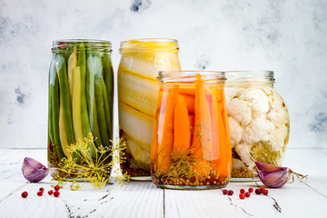 Marinated pickles variety preserving jars. Homemade green beans, squash, carrots, cauliflower pickles. Fermented food.