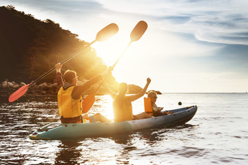 Happy family kayaking sunset sea
