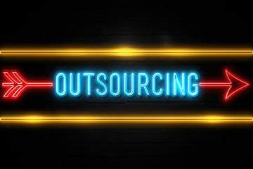 Outsourcing  - fluorescent Neon Sign on brickwall Front view