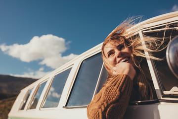 Traveling female driving the van and enjoying road trip Wall mural