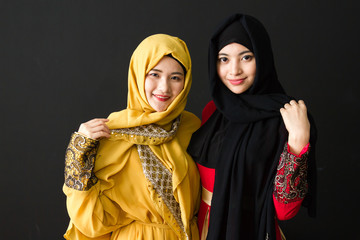 Portrait of Two beautiful young muslim women on a black background.
