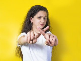 Young pretty brunette girl cross her arms to show gesture no isolated over yellow