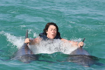 Photo of girl with two dolphin swimming underwater