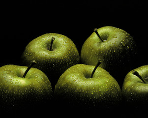 Fresh green apples covered in water droplets on black background