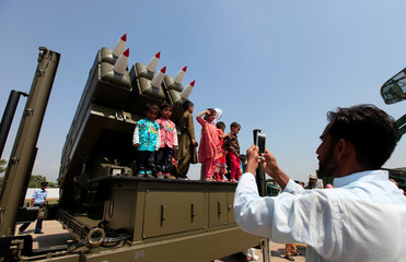A man takes pictures of children standing on a multiple rocket launcher system during a ceremony to commemorate Defence Day, or Pakistan's Memorial Day, at the Nur Khan airbase in Islamabad