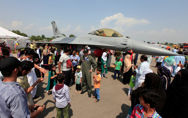 People take pictures with a F-16 fighter jet during a ceremony to commemorate Defence Day, or Pakistan's Memorial Day, at the Nur Khan air base in Islamabad