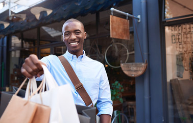 Smiling young man standing on the street holding shopping bags