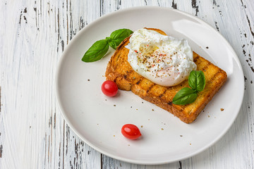 Poached egg on a piece of bread on the wooden table