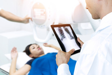 x-Ray or direct radiograph with out film , film-less machine ct scan technology concept. Doctor use tablet for monitoring chest of patient with digital file in smart healthcare hospital.