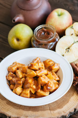 Ingredients for apple pie- salted caramel, slices of apple with caramel sauce, cinnamon sticks on a wooden board. Wooden background, close up and overhead view.