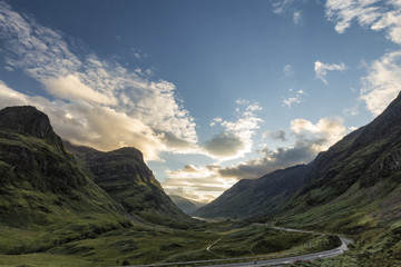 Late afternoon view of the A82 highway snaking its way through the Lost Valley including the The Three Sisters Beinn Fhada, Gearr Aonach, and Aonach Dubh in the Scottish Highlands.