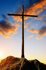 Silhouette wooden cross on the summit of a mountain in the sunset.