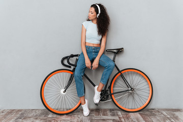 Full length image of beaty curly woman standing with bicycle
