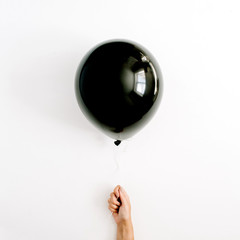 Halloween minimal concept. One black balloon in girl's hand. Flat lay, top view.