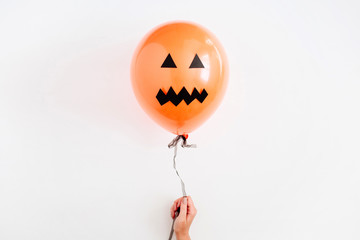 Halloween minimal concept. One orange balloon with scary face in girl's hand on white background. Flat lay, top view.
