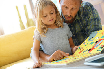 Father and child reading book at home