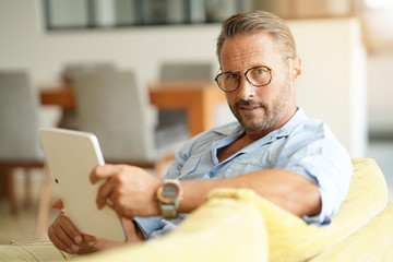 Mature man with eyeglasses connected with tablet at home