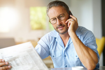 Portrait of mature man with eyeglasses reading newspaper