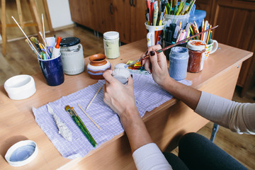 potter woman paints ceramic object. Woman working In her pottery studio. girl draws on a clay object. soft focus on hands