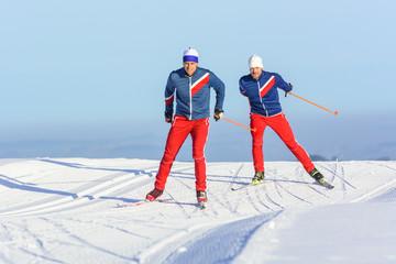 Zwei Skater gleiten auf frisch präparierter Loipe