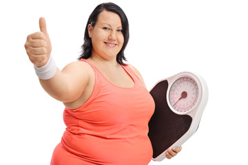 Overweight woman with weight scale making thumb up sign