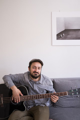 A young man is rehearsing on a bass guitar sitting in a couch