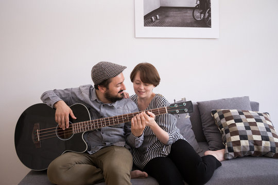 A young man is rehearsing on a bass guitar while the girlfriend is admiring him