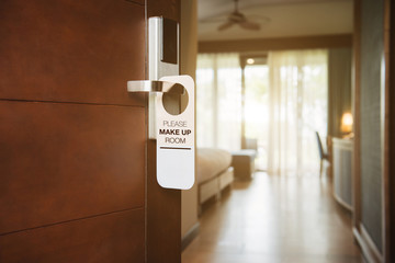 The hotel room with PLEASE MAKE UP ROOM sign on the door