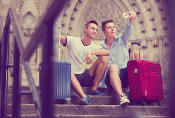 Two guys with luggage  taking selfie in city at summer day