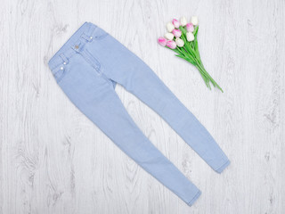 Blue jeans and a bouquet of tulips. Fashionable concept. Wooden background.