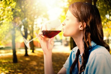 Composite image of woman drinking red wine