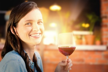 Composite image of smiling woman holding a glass of red wine