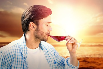 Composite image of man drinking red wine