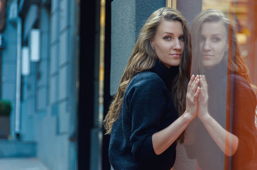 Beautiful slender woman is standing in front of the shop window.