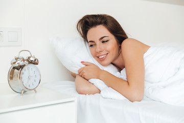 Happy joyful woman laying in bed in the morning
