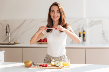 Smiling attractive woman taking a picture of fruit slices