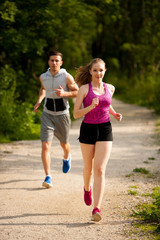 Spoed Fotobehang Jogging Active young couple running in the park