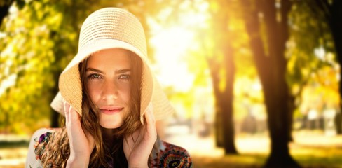 Composite image of portrait of a beautiful girl with straw hat
