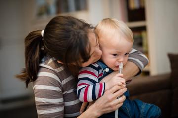 Woman using nasal aspirator for baby