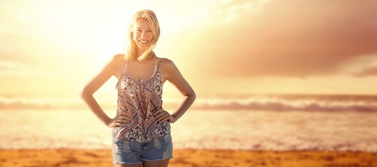Composite image of happy woman with hands on her hips
