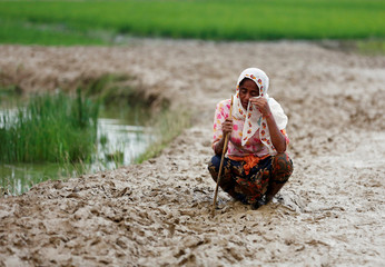 A Rohingya refugee woman wipes her eyes as she cries after crossing the border, in Teknaf