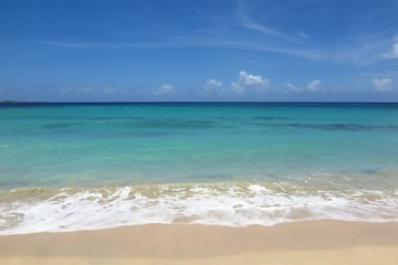 gentle surf laps a sandy beach with turquoise sea and blue sky